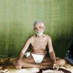 Ramana Maharshi sitzend vor grünem Hintergrund